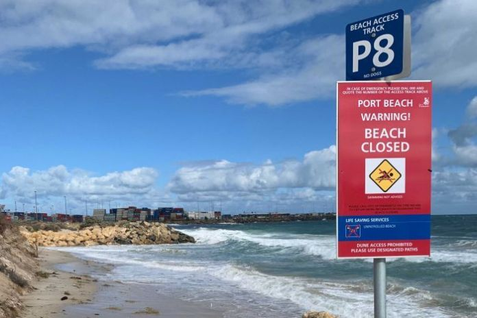 A closed beach sign in a Fremantle beach with the harbor in the background.