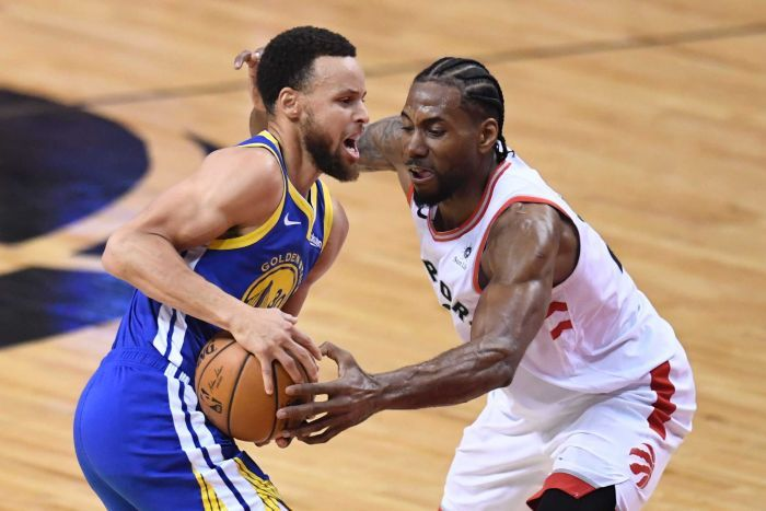 Stephen Curry holds the ball at hip level as Kawhi Leonard uses his left hand to try to steal the ball.