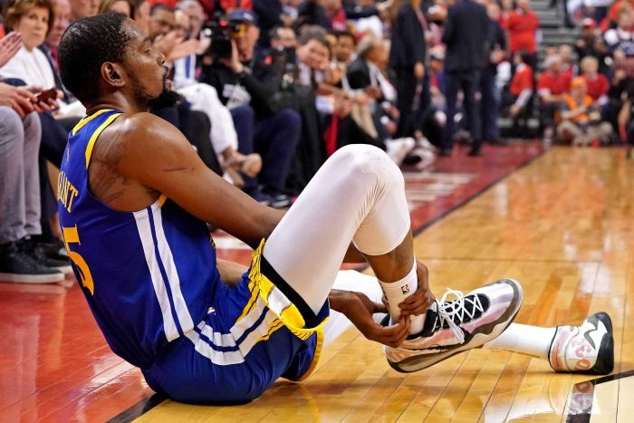 An injured basketballer sits on the court.