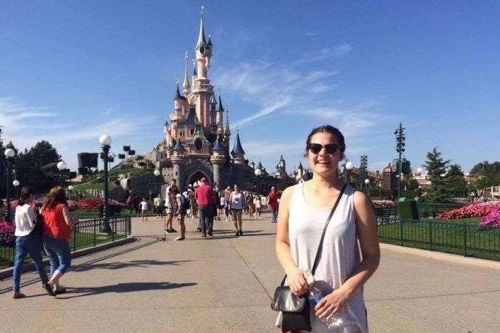 Ella Ingram, wearing sunglasses stands in front of disneyland castle.