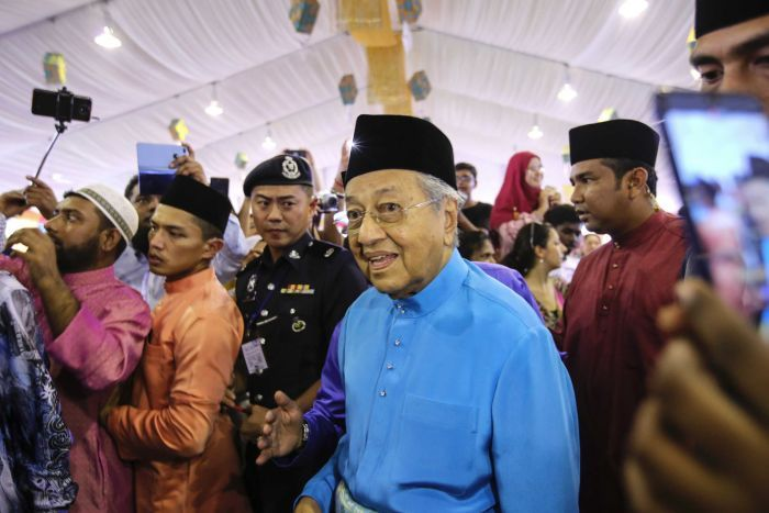 Malaysian Prime Minister Mahathir Mohamad arrives for an Eid celebration in traditional clothing.