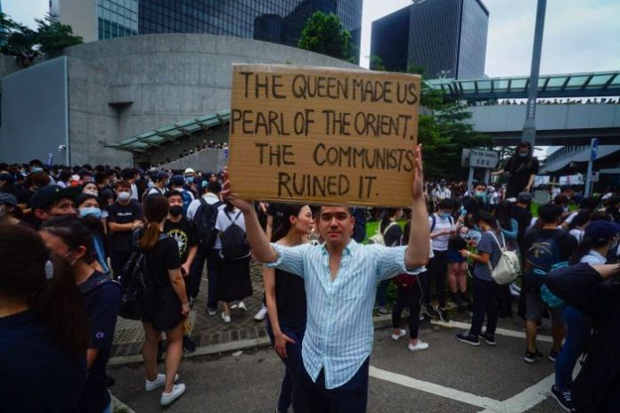 """A man holds up a sign that says """"The queen has turned us into the Pearl of the East. The communists have ruined it""""."""