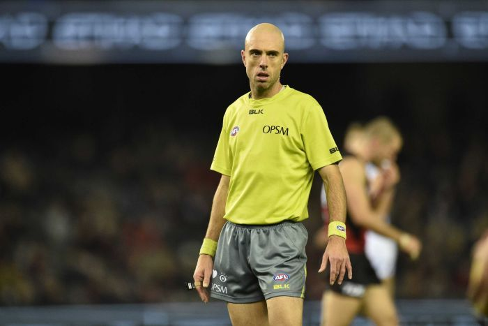 AFL umpire Mathew Nicholls stands and looks at the play while holding his whistle.