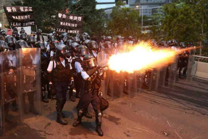 Police officers launch tear gas during a demonstration against an extradition proposal in Hong Kong.