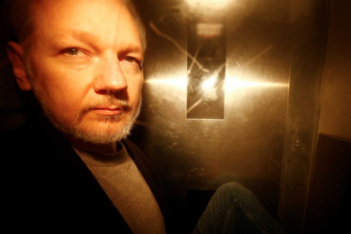 A photo of Julian Assange taken through the window of a police van