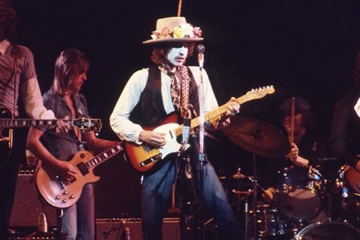 Bob Dyan with white paint on his face, wearing a straw hat decorated with flowers, plays a guitar on stage