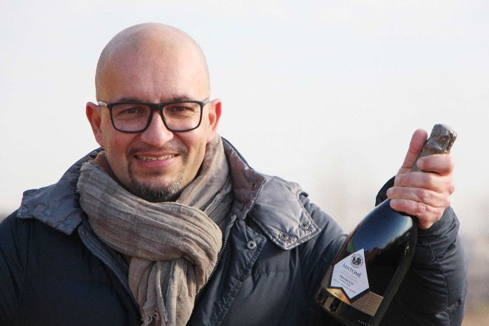 William Spinazze holding a bottle of Santome Prosecco Brut in valley of vineyards, Italy.