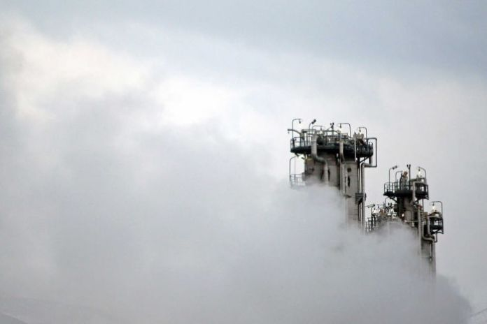 A heavy Arak water production plant surrounded by smoke