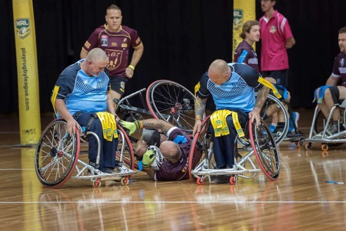 A group of people playing wheelchair rugby.