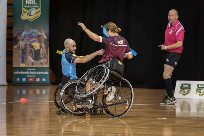 Two men playing football in wheelchairs with one chair up on one wheel.