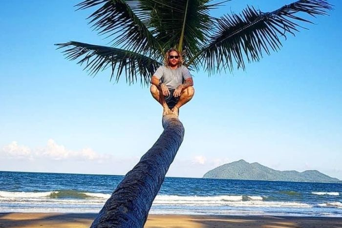 Mr Thomson sits mid-way up a palm tree on the beach with ocean in the background.