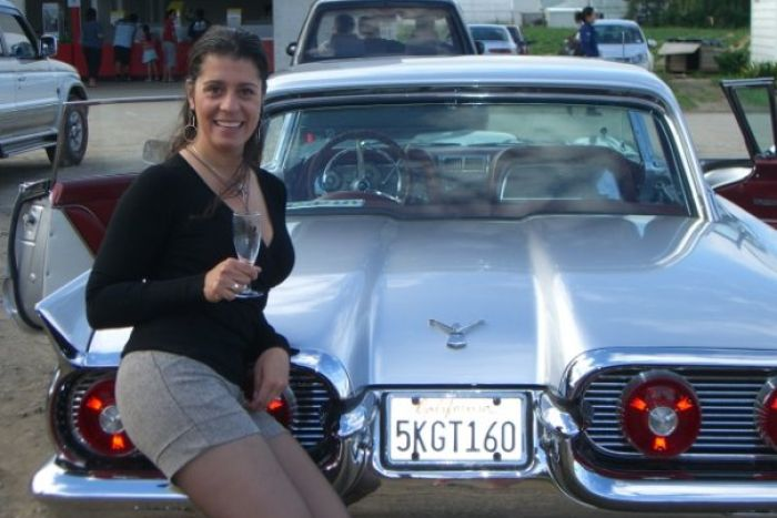 A woman with a black top holding a glass of champagne leaning on a silver classic car.