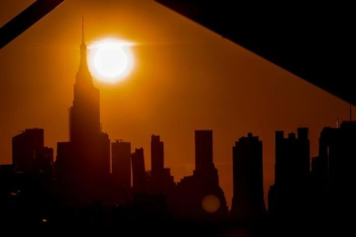 The skyline of the city of New York is seen obscured by the sun above the Empire State Building, with a yellow glow on it.