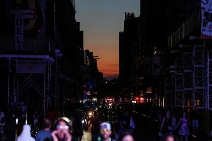 The buildings are immersed in the darkness to the left and right with people walking in front of the camera and the sun setting in the distance.