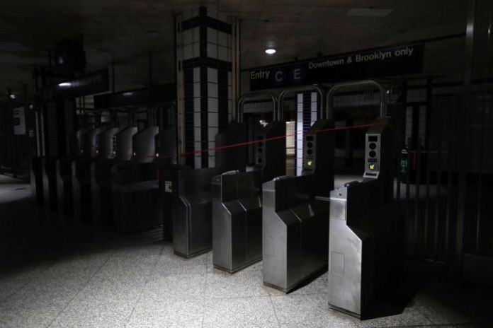Entrance barriers to the subway are shrouded in darkness.