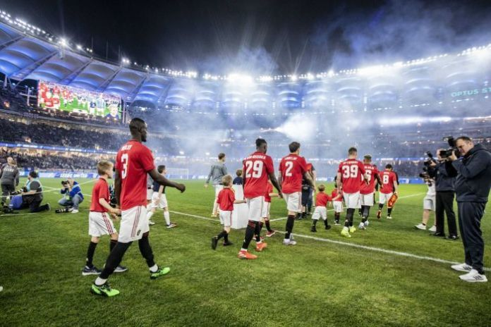 Manchester United and Leeds United come out at the Perth stadium under the lights.