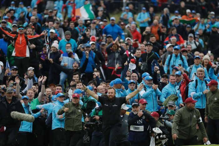 A large crowd celebrates, an Irish flag flies and Shane Lowry stands in front of it all with his arms raised.