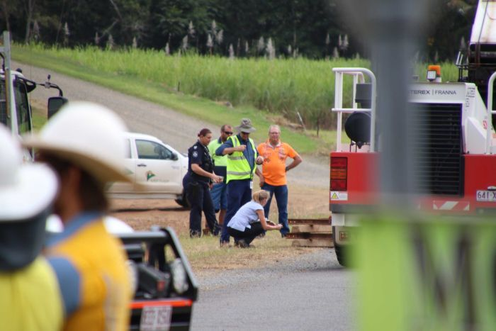 Police and workplace investigators stand together looking at a crane