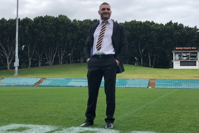A man stands in a suit as he smiles while standing on a rugby league field.