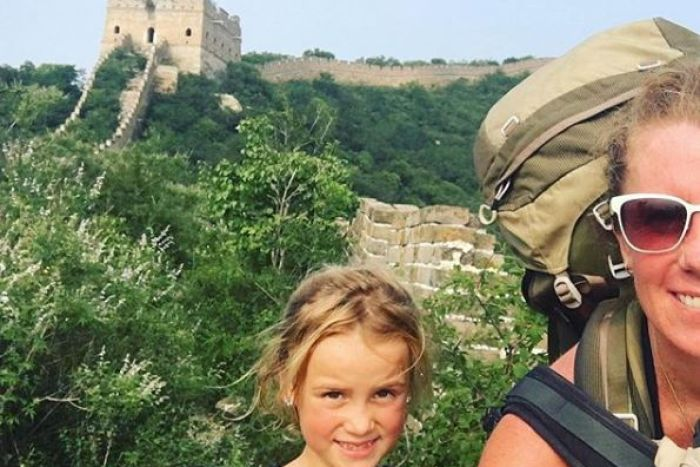 A selfie photo of a mother backpacking with her daughter on the Great Wall of China.