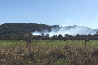 Smoke seen from a distance blows over paddocks and hills in a green area.