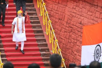 Mr Modi, wearing white and orange, walks down a red carpet staircase at the Red Fort in Delhi.