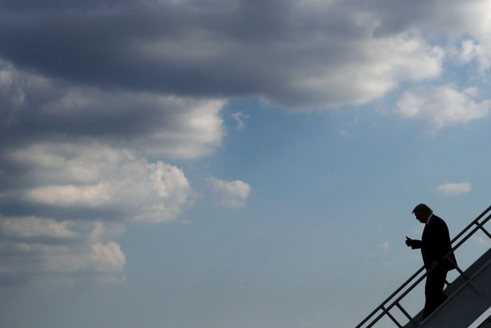 US President Donald Trump walks down stairs off an airplane with storm clouds in the distance