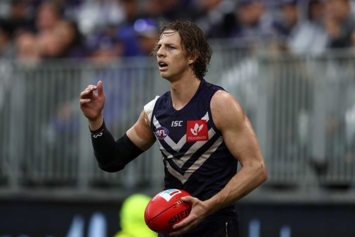 Nat Fyfe raises his hand while holding the ball.