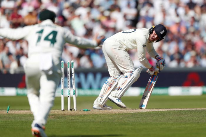 Jason Roy looks back at his broken stumps while completing an unsuccessful shot. And Australian celebrates in the foreground.