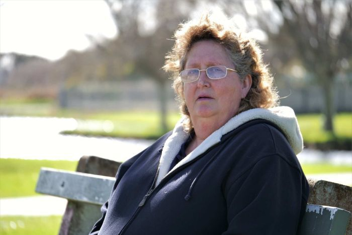 A woman sitting on a park bench with an anguished expression.