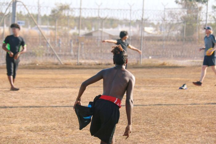 A young indigenous man with his back to camera is running in a game of football, in the background are high fences.