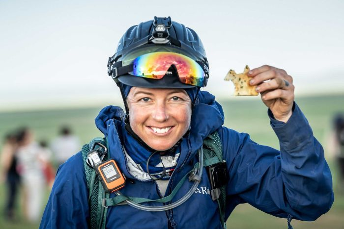 A woman out in a field wearing a horse riding helmet smiles holding a biscuit.