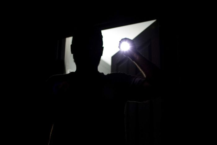 A silhouette of a man is seen as he shines a torch into the camera.