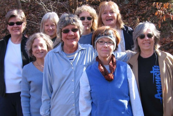 A group of eight women casually dressed stand close together, smiling and looking towards camera, with scrub in the background.