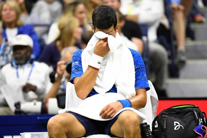 A male tennis player sits in a chair while holding his face in a towel.