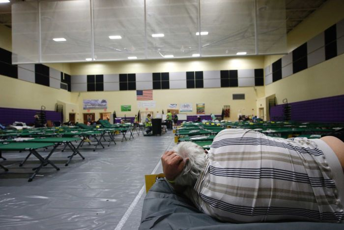A man lies on one of countless cots set up in rows in a large building.