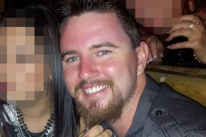 A smiling man with a goatee beard in a nightclub next to two women whose faces are pixelated.