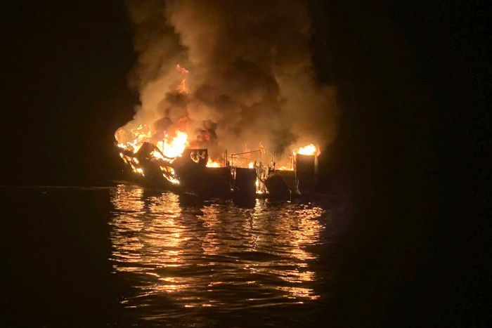 A boat engulfed in fire and smoke during night time.