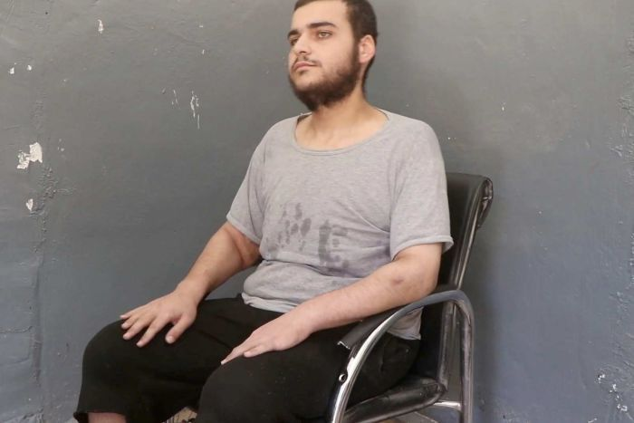 Hamza Elbaf sits in a black chair against a grey wall.