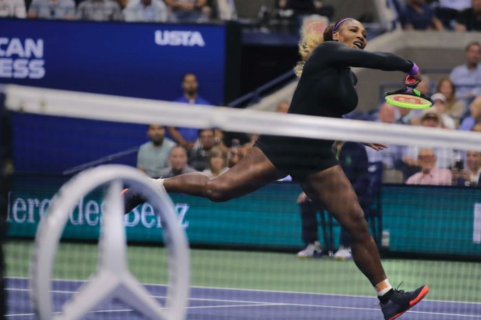 A tennis player in full stride completes her follow-through after hitting the ball over the net.