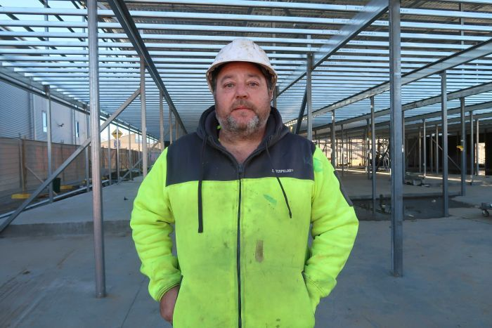 Roofer David Panetta wearing high-vis jacket and hard hat, standing in the metal framework of an industrial building