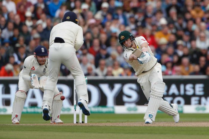 Silly point leaps while the ball goes past him. Steve Smith is eyeing the ball intently as he completes his cover drive.