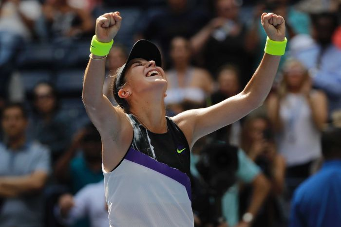 Belinda Bencic tilts her head up to the sky with her eyes closed and mouth open and both arms up with fists clenched