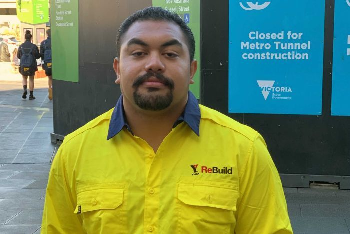 A man wearing a bright yellow work shirts stands near a  Metro Tunnel construction site.