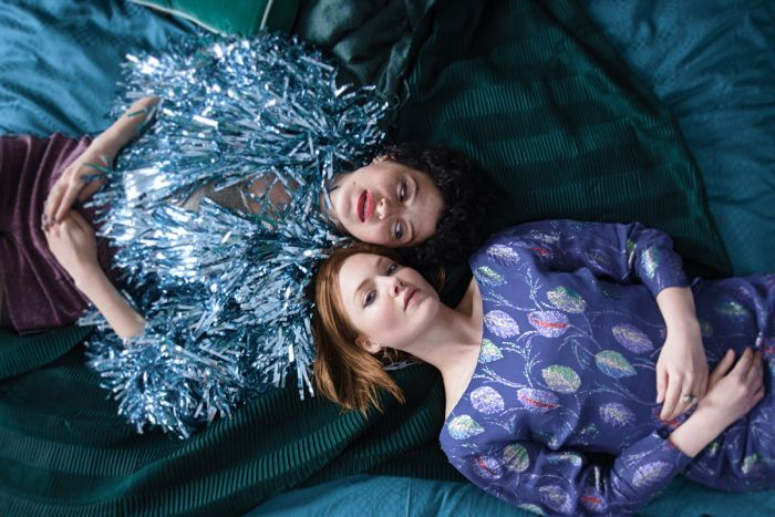 Two women, one wearing a bright coloured tassel jacket the other a patterned dress, lie on their backs on bed with heads close.