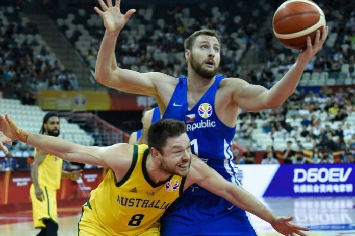 Two players fight for a basketball during a game.