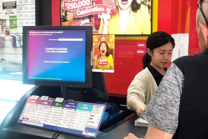 Staff serve a customer beside computer screen that says 'congratulations, you are a winner' at newsagency.