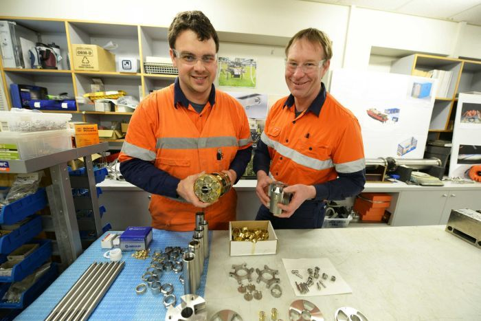 Two AAD employees in high-vis gear hold parts of an ice core drill