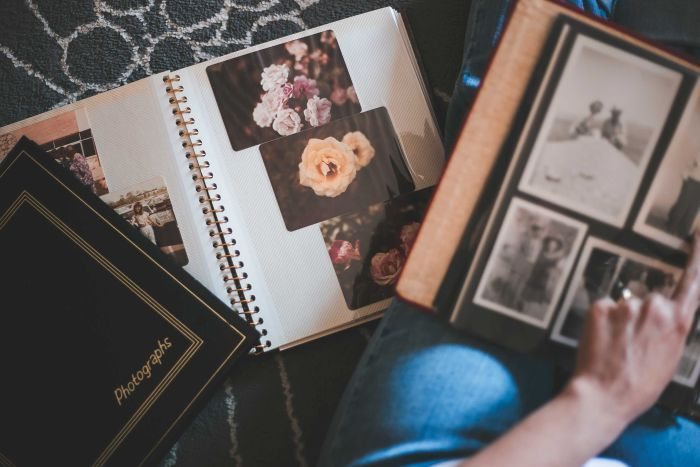 Old photo albums open on a floor with hand pointing to an image.