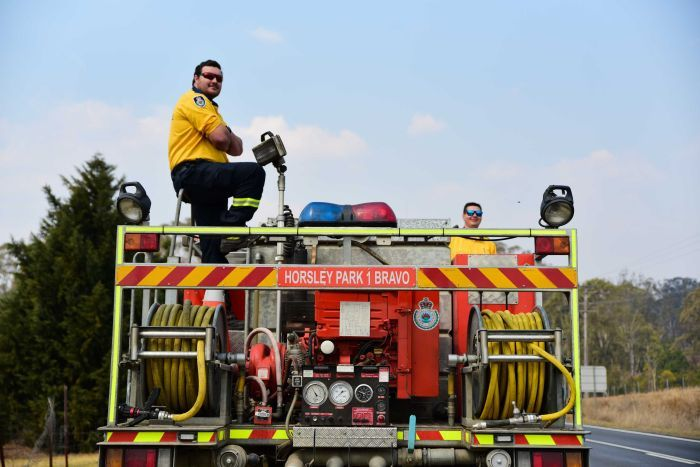 A man stands on top of a fire engine, he is wearing a RFS polo-shirt and sunglasses.